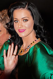 A picture of a woman wearing a green metallic dress and long black hair
