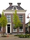 foto van Pand met verdieping en forse rechte kroonlijst met ronde dakvensters onder U-vormig schilddak met twee hoekschoorstenen waarop borden