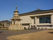 A model of a stone pagoda on the left and an ivory building with a cursive dark blue roof on the background