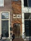 foto van Geprofileerd bakstenen poortje met gevelsteen met paard en koe en opschrift