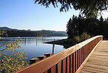 A Pedestrian Bridge Crosses Lewis Creek At Park Along Foster Reservoirs North Shore