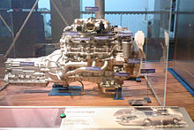 Side view of a V8 engine and transmission, with exposed components and identification labels attached.