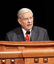 Photo of M Russell Ballard standing behind a podium giving a speech.