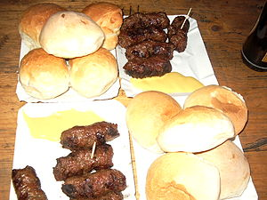 Romanian cuisine - Mititei, mustard, and bread rolls