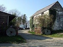 millstones leaning against old farm buildings
