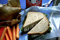 A lunch sits on a blue tablecloth with a brown paper bag and red napkin. There are carrots, a pear, a sandwich on wheat bread with lettuce (chicken salad) and a carton of milk.