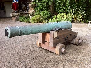 HMS Association (1697) - This French 18-pounder bronze gun, probably a trophy from the siege of Toulon (1707) was recovered from the Association site in 1970. The main decoration shows the arms of France and Navarre surrounded by the collars of the orders of St Michel and the St Esprit, surmounted by a crown. The gun carriage is modern. In the Valhalla Museum in Tresco Abbey Gardens, Isles of Scilly.