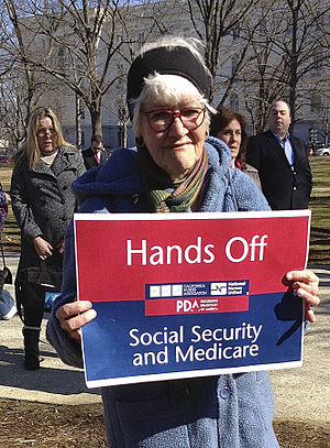 "Social Security debate in the United States - Nurse with sign, ""Hands off Social Security and Medicare,"" at a rally in Senate Park, Washington D.C., 2013."