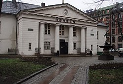 Photograph showing the main entrance to the Oslo Børs, known in English as the Oslo Stock Exchange in Norway. The building is in the Renaissance architectural style, its exterior painted in an Ivory white colour. Its entrance is protected by an imposing porch topped with a triangular pediment supported by four columns.