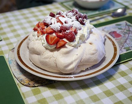 The meringue-based pavlova is generally eaten at Christmas time. Pavlova garnished with cream and strawberries.jpg
