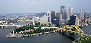 A view of a city nestled at the point where two rivers merge. There are yellow bridges crossing the rivers and a large fountain at the point where they meet. The city steps back from a park surrounding this fountain.