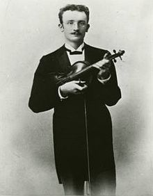 A thirtysomething man in a tuxedo and glasses clutches a violin and gazes at the camera