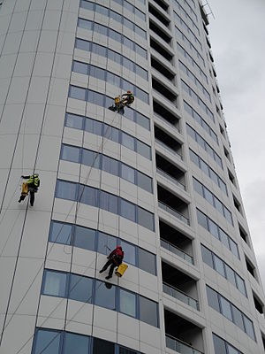 Window cleaners in safety harnesses cleaning w...