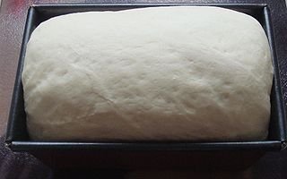 Risen bread dough in tin.jpg