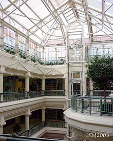 Interior of multi-storey shopping centre atrium with glass roof