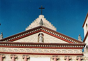 a close up view of the pediment situated above the chapel entrance at mission santa barbara and its unique ornamental frieze