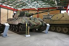 A three quarters view of a large tank with a flat-faced turret, dull yellow, green and brown wavy camouflage, on display inside a museum. The frontal armour is sloped, the long gun overhangs the bow by several meters. Two waist-high cartridges sit on their bases in front of it.