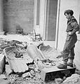 Sergeant R S Baker of the Army Film & Photographic Unit (AFPU) looks at a fallen Nazi eagle and swastika amidst the ruins of Hitler's Reich Chancellery in Berlin, 3 July 1945. BU8560.jpg