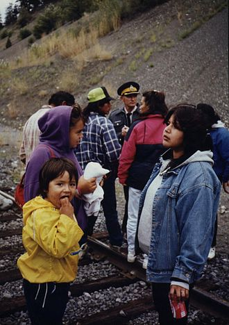 Members of the Seton Lake Indian Band blockade the BC Rail line in support of Oka, while a Royal Canadian Mounted Police officer looks on. Later in the day, several of the elders protesting were arrested and a confrontation with the band community ensued as mounties marched the squad cars holding those arrested through the reserve en route to Lillooet. Seton blockade.jpg