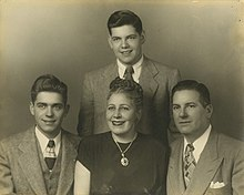 A portrait of a teenage Silvers standing behind seated family members