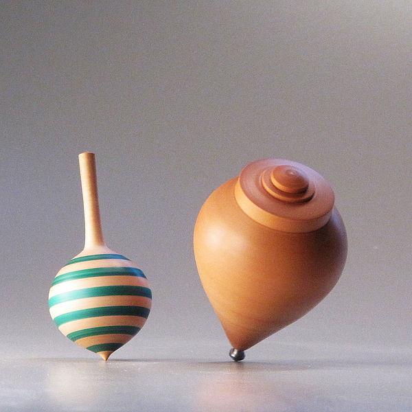 due trottole di diverso utilizzo, la prima color legno a bande verdi è del tipo che gira tra le dita, la seconda, color legno e più grande, viene lanciata