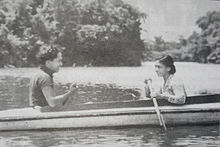 A black-and-white photograph of a man and a woman in a boat