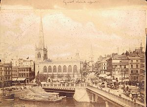 St Nicholas, Bristol - Black and white photograph from c.1900 showing the south view of St Nicholas church, Bristol, UK, in the context of Bristol Bridge, Welsh Back, and the 'Castle' district (now Castle Park). Other church spires visible in the photograph are All Saints' Church and Christ Church. In the foreground on the bridge can be see trams and horse-drawn wagons.