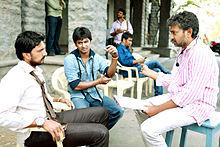 Sudeep and Nani sit in chairs and listen to Rajamouli.