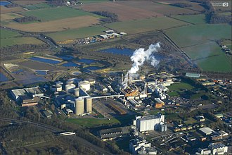 Sucrose - A table sugar factory in England. The tall diffusers are visible to the middle left where the harvest transforms into a sugar syrup. The boiler and furnace are in the center, where table sugar crystals form. An expressway for transport is visible in the lower left.