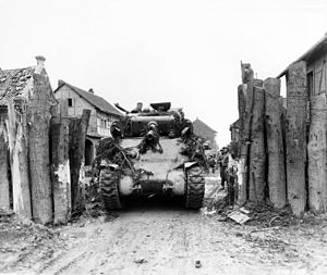 745th Tank Battalion - Tank of the 745th Tank Battalion, attached to the 1st Infantry Division, U.S. First Army, rolls through former German block in Gladbach, Germany.
