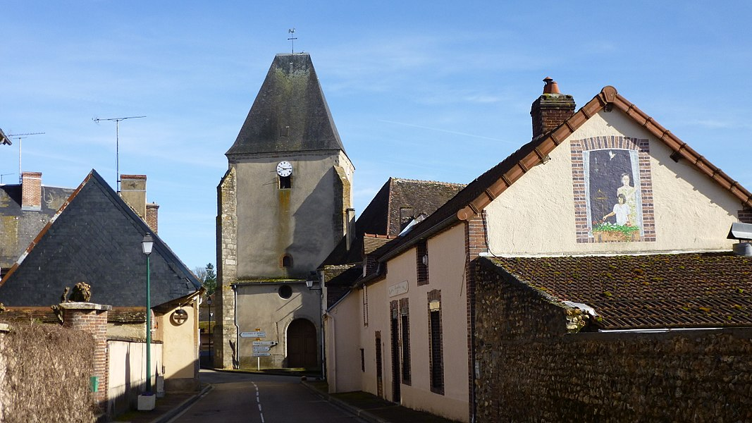 Tannerre-en-Puisaye, Yonne, Burgundy, France.  Coming from Champignelles on the D 7, in rue Carreau with the church in perspective. At n° 5 of that street, a trompe-l'oeil painting on a house end wall, representing a woman and a child loking through a window. The same house has another trompe-l'oeil painting on its façade, representing a woman leaning on a window-sill.