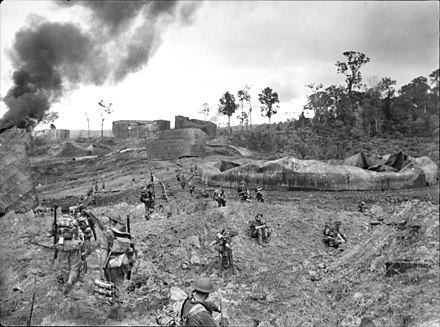 Infantry from the 2/23rd Infantry Battalion advancing through wrecked oil storage tanks at Tank Hill, Tarakan. (AWM 090932) Tarakan 1945 AWM 090932.jpg