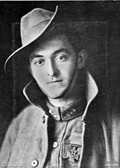 Portrait photograph of soldier wearing a medal shaped like a cross on his left breast. He is wearing a slouch hat and a greatcoat that is unbuttoned