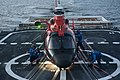U.S. Coast Guard flight deck crew members aboard maritime security cutter USCGC Bertholf (WMSL 750) tie down an MH-65 Dolphin helicopter arriving from Coast Guard Air Station Los Angeles to the deck to secure it 120822-G-VS714-324.jpg