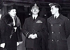 Three-quarter outdoor portrait of moustachioed man in military uniform with peaked cap and pilot's wings on left breast pocket, flanked by woman in hat and fur coat, and young man in military great coat and forage cap