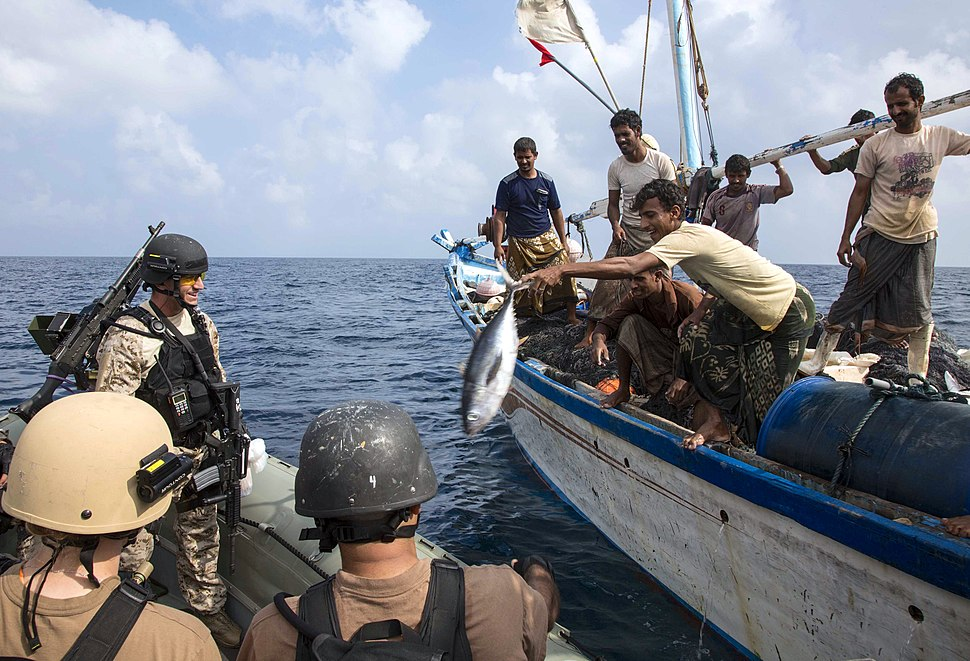USS Mason (DDG 87) VBSS team receive a fish from a Yemeni fisherman