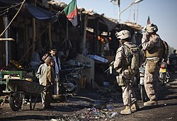 Two Marines stand off to the side of a road near several dilapidated buildings while talking to a group of small children.