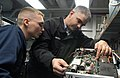 US Navy 070117-N-9116H-002 Aviation Electronics Technician 1st Class Michael McCann trains Aviation Electronics Technician Airman Scott Hoag on calibration procedures for an oscilloscope aboard USS Theodore Roosevelt (CVN 71).jpg