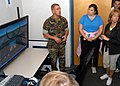 US Navy 070718-N-9860Y-030 Navy Diver 1st Class Paul Mehring, of Portland, Ore., describes how aviation personnel use the reduced-oxygen breathing device in relation to a flight simulator to a group of educators from Texas in t.jpg