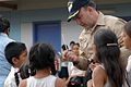 US Navy 070723-N-7088A-015 Capt. Bob Kapcio, mission commander aboard Military Sealift Command hospital ship USNS Comfort (T-AH 20), passes out pencils to children at the El Realejo Health Care Center.jpg