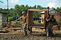 US Navy 080607-N-7498L-287 Seabees assigned to Naval Mobile Construction Battalion (NMCB) 133 and Armed Forces of the Philippines soldiers from the 546th Engineer Construction Battalion carry a wooden form to the construction s.jpg