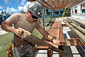 US Navy 080823-N-1328S-001 Builder 2nd Class Gabriel Kelley, assigned to Navy Mobile Construction Battalion (NMCB) 133, cuts wood planks for the reconstruction of Mwan Elementary School during a Pacific Partnership engineering.jpg