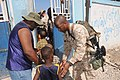 US Navy 100125-N-5700G-567 Marine Staff Sgt. Christopher D. Thomas, from Franklin, La., guides children to a humanitarian aid distribution point in Saint Marc, Haiti.jpg