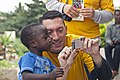 US Navy 110818-N-XK513-070 A Sailor shares photos with a Ghanaian child.jpg