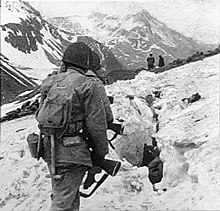 A line of soldiers hiking on the side of a snow-covered mountain, viewed from behind