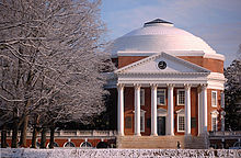 A red brick, Neoclassical dome with a large portico on the front and covered walkway on the sides. Snow covers the foreground and trees.