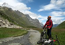 man with mountain bike looking up towards Mont Blanc
