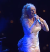 A woman with blond hair is wearing a white dress and is singing on a stage