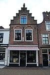 foto van Huis met trapgevel met geblokte ontlastingsbogen, muurankers en granaatappel als topversiering