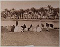 Vrouwen putten water in kruiken uit de Nijl, op de achtergrond is de overkant van de rivier te zien met palmbomen- Stichting Nationaal Museum van Wereldculturen - TM-60062740.jpg
